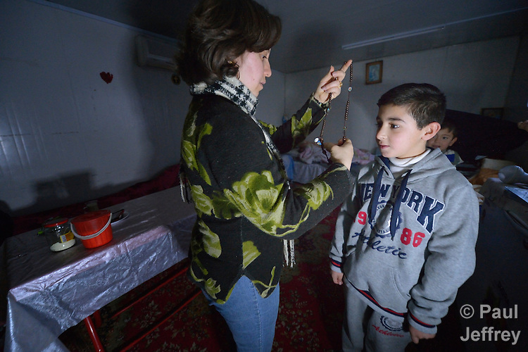 Roaa Sabah kisses places a crucifix on her 10-year old son Behnam as he prepares to leave for school early in the morning from their home in Seje, Iraq. The community was flooded with displaced families when the Islamic State group took over nearby portions of the Nineveh Plains in 2014, including this family, which fled from Mosul to eventually live in a small, manufactured housing unit in Seje. Because Behnam and other displaced children came from communities with Arabic curriculum schools, they don't fit well in local schools that teach in Kurdish or Assyrian, so the Christian Aid Program Nohadra - Iraq (CAPNI) provides transportation for them to Duhok, where they study in schools that meet their needs.