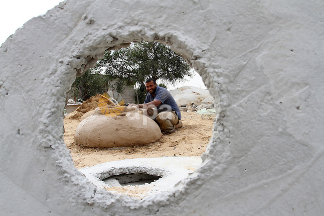 A Palestinian man, Iyad Abu Samhadana, prepares the clay ovens to earn their living, in Rafah in the southern Gaza Strip, on November 27, 2016. Photo by Abed Rahim Khatib