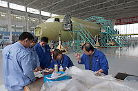 Chinese engineers check the parts as they build an ARJ21 passenger plane at a factory of Shanghai Aircraft Manufacturing Company in Shanghai, China on November 12, 2009.