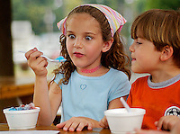 Claire Beaulieu finds something interesting in her snow cone sundae, while her brother Julien watches at the Carousel Frozen Treats Stand 7-28-04 in Warrenton, VA.