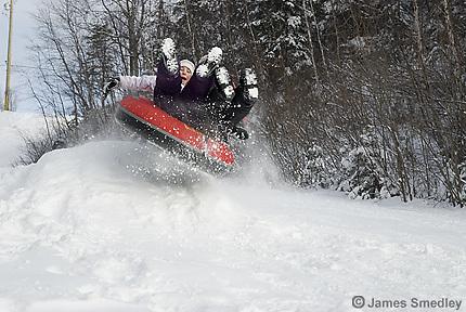 Kids sledding or toboganning down a hill in winter