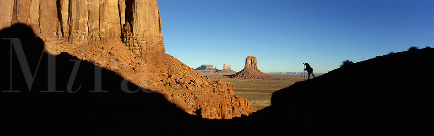 Panoramic landscape of Monument Valley, the distant figure of a photographer in silhouette on the rock formation to the right. Arizona.