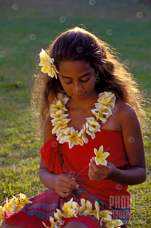 Pretty young local girl strings a yellow plumeria lei wearing a red sarong.