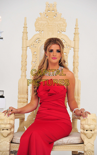 Lucy Mecklenburgh.Lucy Mecklenburgh photocall. The Only Way is Essex star launches her debut Jewellery collection, The Worx, London, England..November 20th, 2012.TOWIE half length red strapless dress necklace jewelry  silver red green stones  sitting throne .CAP/BF.©Bob Fidgeon/Capital Pictures.