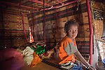 In the seasonal village of Bantagiri in northern Burkina Faso, a Fulani woman sits with her children inside a straw mat house.  The Fulani are traditionally nomadic pastoralists, crisscrossing the Sahel season after season in search of fresh water and green pastures for their cattle and other livestock.  The straw mat house can be reassembled and dissasembled at will.