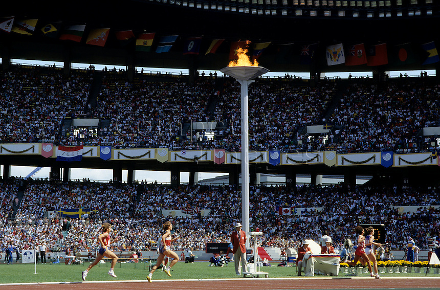 Olympic torch stands above an athletic field holding events