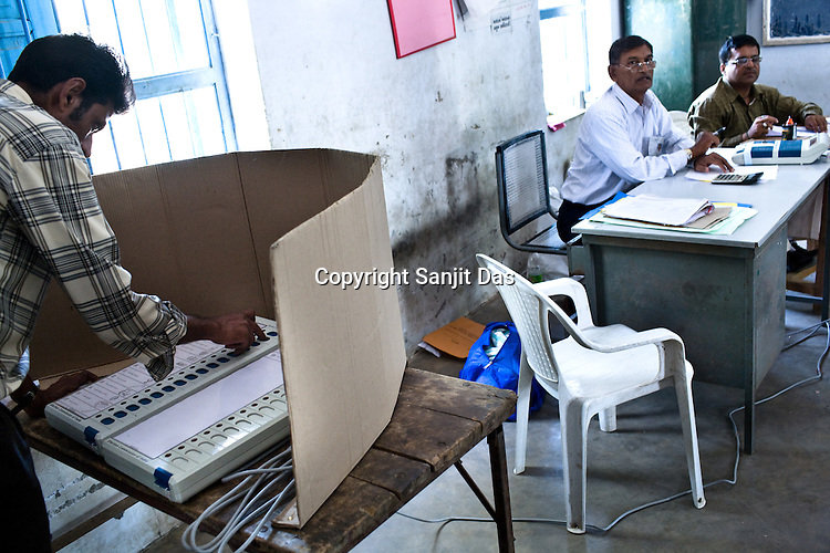 A voter is seen casting his vote on the electronic polling machine in a polling booth in Government school building in Ghuma village of Rural Ahmedabad, Gujarat India. About 49 per cent of the 3.65 crore electorate today exercised their franchise in the single phase polling in the state's 26 Lok Sabha constituencies on April 30th 2009.