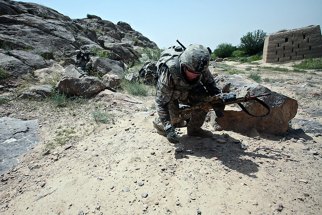 Staff Sgt. Richard Guynes, a soldier with Company A, 2nd Battalion, 2nd Infantry Regiment, scrambles for better cover after his patrol is attacked by Taliban fighters near the village of Zangabad in Panjwayi district, Kandahar province, Afghanistan. April 27, 2009. DREW BROWN/STARS AND STRIPES