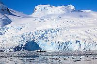 A zodiac provides safety for a group of sea kayakers at Cierva Cove along the Antarctic Peninsula.