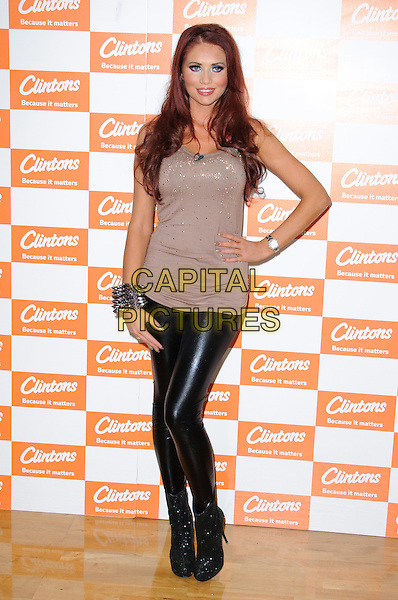 Amy Childs.Former TOWIE star meets the fans and signs copies of her Official 2012 Calendar at Clintons, Bluewater shopping center, Kent, England, .12th November 2012..full length  leather pvc shiny  brown beige  top t-shirt  ankle boots hand on hip .CAP/CJ.©Chris Joseph/Capital Pictures.