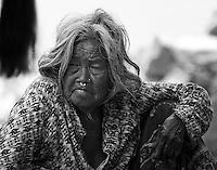 An elderly beggar sits at the base of Swayambhunath Temple in Kathmandu, Nepal.