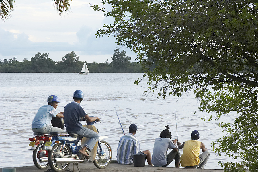 Local residents of mixed descent (African and Javanese) on the shore of the Suriname River in the capital city of Paramaribo, Suriname.