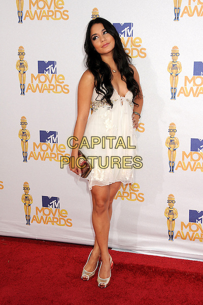 VANESSA HUDGENS .MTV Movie Awards 2010 - Arrivals held at the Gibson Amphitheatre, Universal City, California, USA, 6th June 2010..full length white dress gold clutch bag shoes peep toe hand on hip beaded cream layered layers tiered .CAP/ADM/BP.©Byron Purvis/AdMedia/Capital Pictures.