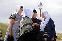 Nederland  Katwijk 2016   .Een dagje naar het strand. Noordzee Zomerfestival. Nationaal Klederdracht Festival. Links drie vrouwen in klederdracht uit Zeeland. Rechts klederdracht uit Emmen.  Foto Berlinda van Dam / Hollandse Hoogte