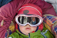 Sweden, SWE, Kiruna, 2008Mar22: A one year old girl wearing ski glasses lies in a buggy, well protected against the cold.