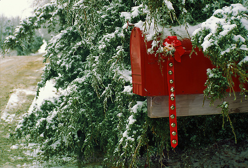 Red mailbox decorated for Christmas with jingle bells