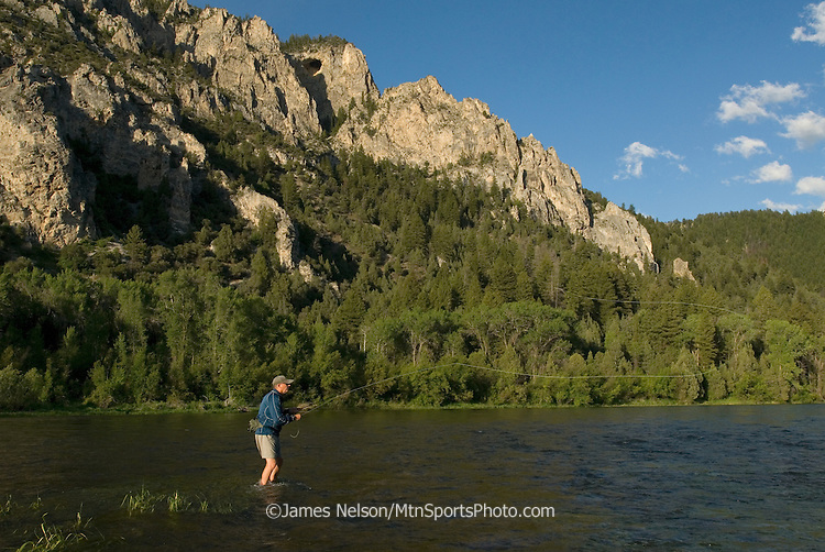 """An angler casts a fly for trout during a summer afternoon on the """"canyon section"""" of the South Fork of the Snake River, Idaho."""
