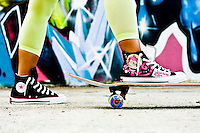 Female standing in Chuck Taylor's on a skateboard in front of a graffiti wall