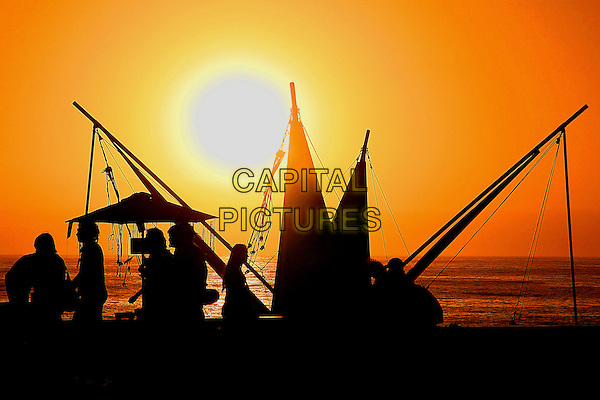 ATMOSPHERE .People walk by market stalls along the beach of Renaca , Chile,.20th February 2008..travel sun sunset set .CAP/GH.©Gardner Hamilton/Capital Pictures