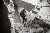 In this Friday, Nov. 02, 2012 photo, a rebel fighter walks across the debris of shattered house buildings at the battlefield in Karmal Jabl after several days of intense fighting between rebel fighters and the Syrian army in Aleppo, the Syrian's largest city. (AP Photo/Narciso Contreras).