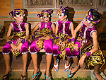 14 JULY 2016 - UBUD, BALI, INDONESIA: Boys in a traditional Balinese legong dance troupe wait to perform during the mass cremation ceremony in Ubud. Local people in Ubud exhumed the remains of family members and burned their remains in a mass cremation ceremony Wednesday. Thursday was spent preparing for Saturday's ceremony that concludes the cremation and included traditional Balinese Legong dances performed in the evening. Almost 100 people will be cremated and laid to rest in the largest mass cremation in Bali in years this week. Most of the people on Bali are Hindus. Traditional cremations in Bali are very expensive, so communities usually hold one mass cremation approximately every five years. The cremation in Ubud will conclude Saturday, with a large community ceremony.   PHOTO BY JACK KURTZ