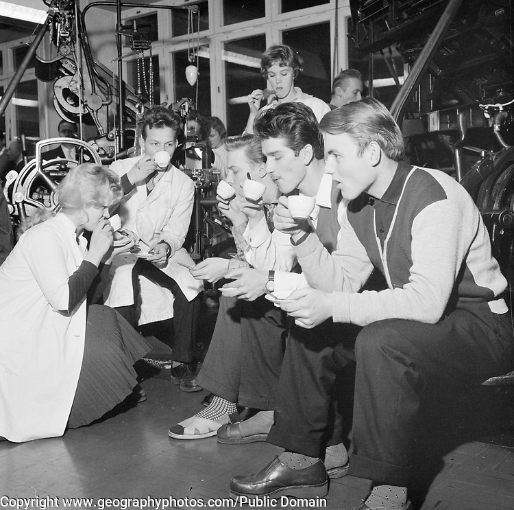 Young people male and female workers in printing factory drinking coffee, Finland 1959