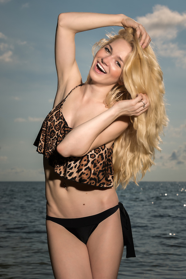 Happy blonde caucasian girl laughing in the beach early morning with arm raised and looking at camera.