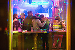 © Joel Goodman - 07973 332324 . 11/09/2016 . Manchester , UK . View through the window of men hugging close together , inside Yates Wine Lodge on Portland Street . Revellers out in Manchester City Centre . Photo credit : Joel Goodman