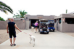 "Bill Pearson, 62, with his standard poodle Phoenix and Lori Pearson with Sedona outside of their home in Sun City, Arizona August  2010. His mother also lives in Sun City, so he is a second-generation Sun Citian, which is very common. ""I saw it and I said this is how and where I want to grow old,"" Bill said about his first visit to Sun City with his wife Lori...2010 marks the 50th anniversary of the United States' first planned retirement city. When Del Webb created Sun City and it opened in 1960, it was a revolutionary idea for retirees to move away from home and to live extremely active and social lifestyles.."