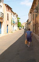 Domaine d'Aupilhac. Montpeyroux. Languedoc. The winery building with a person walking in the shade on the street. France. Europe.