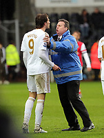 Pictured: Michu of Swansea (9) is held back by a stadium steward during what seems to be a verbal argument with Arsenal goalkeeper Lukasz Fabianski (not pictured).  Saturday 16 March 2013<br />