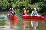 Four young adults in two canoes paddle side by side down the Fox River in Yorkville Illinois USA