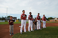 "General view of Batavia Muckdogs J.J. Gould (49), Samuel Castro (25), Rony Cabrera (26), and Eric Gutierrez (43) stand for the national anthem with ""Stars of the Game"" participants before a game against the Brooklyn Cyclones on July 4, 2016 at Dwyer Stadium in Batavia, New York.  Brooklyn defeated Batavia 5-1.  (Mike Janes/Four Seam Images)"