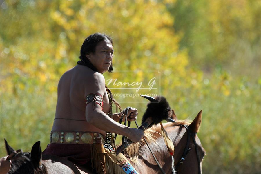 A Native American Indian man on horseback walking through a river