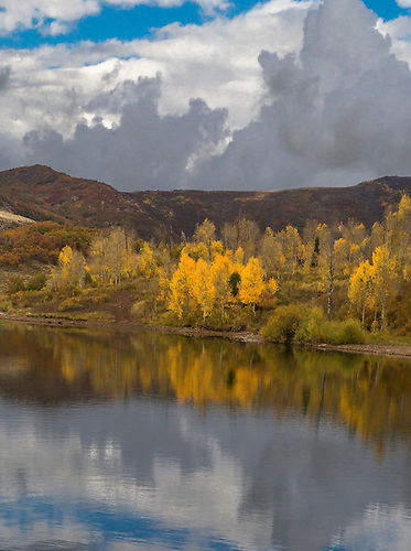 Fall colors from Aspen trees are reflected in the still waters of Kolob Reservoir near Zion National Park, Utah