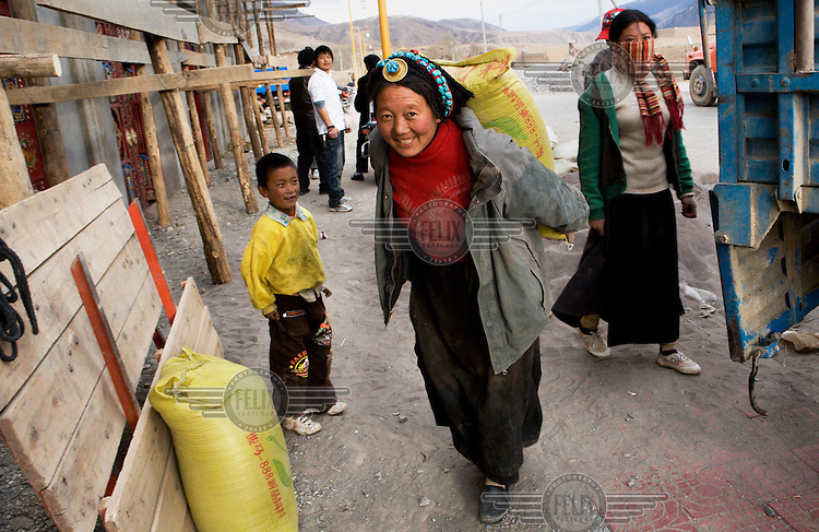 A woman carries building materials to construct a new home.