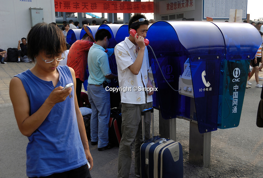 A chinese man checks his cell phone while some others use telephone at CNC booth in Tianjin railway station, China..