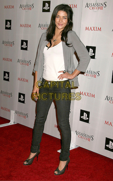 JESSICA SZOHR.at the Maxim And Ubisoft Celebrate The Launch Of 'Assassin's Creed II' held At Voyeur, West Hollywood, California, USA, 11th November 2009.full length grey gray jacket hand on hip jeans denim skinny shoes peep toe heels white top t-shirt ring .CAP/ADM/MJ.©Michael Jade/AdMedia/Capital Pictures.