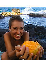 A young local woman holds a partially peeled mango in front of her with Makapu'u tide pools in the background, East O'ahu.