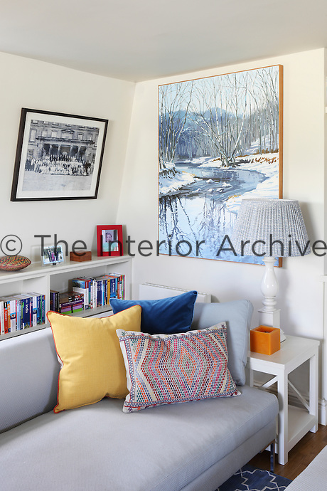 A built-in bookcase contains numerous travel books behind a pale blue sofa in this sitting room