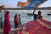 India. Uttar Pradesh state. Allahabad. Maha Kumbh Mela. Two women, both Indian Hindu devotees, are drying their sarees after taking a holy dip in Sangam. A couple stands close to the water. The Kumbh Mela, believed to be the largest religious gathering is held every 12 years on the banks of the 'Sangam'- the confluence of the holy rivers Ganga, Yamuna and the mythical Saraswati.  In 2013, it is estimated that nearly 80 million devotees took a bath in the water of the holy river Ganges. The belief is that bathing and taking a holy dip will wash and free one from all the past sins, get salvation and paves the way for Moksha (meaning liberation from the cycle of Life, Death and Rebirth). Bathing in the holy waters of Ganga is believed to be most auspicious at the time of Kumbh Mela, because the water is charged with positive healing effects and enhanced with electromagnetic radiations of the Sun, Moon and Jupiter. The Maha (great) Kumbh Mela, which comes after 12 Purna Kumbh Mela, or 144 years, is always held at Allahabad. Uttar Pradesh (abbreviated U.P.) is a state located in northern India. 7.02.13 © 2013 Didier Ruef