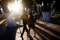 Puebla, Mexico - DEC 2: A couple of young lovers stroll through the afternoon light in the zocalo on December 2, 2008, in Puebla, Mexico. (Photo by Landon Nordeman)