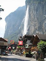 A mountain waterfall cascades over the Swiss Alps village of Lauderbrunnen