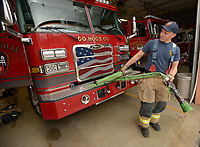 NWA Democrat-Gazette/ANDY SHUPE<br /> Martin Striefler, firefighter with the Fayetteville Fire Department, rewinds a hose Thursday, March 29, 2018, in the department's central fire station. The City Council will take up a proposal Tuesday for citywide raises, which includes a new pay structure for police and firefighters.