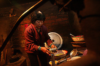 Farmer Cong Peiling, 54, cooks noodles on a stove in Yongfu, on February 27, 2006. Photo by Lucas Schifres/Pictobank