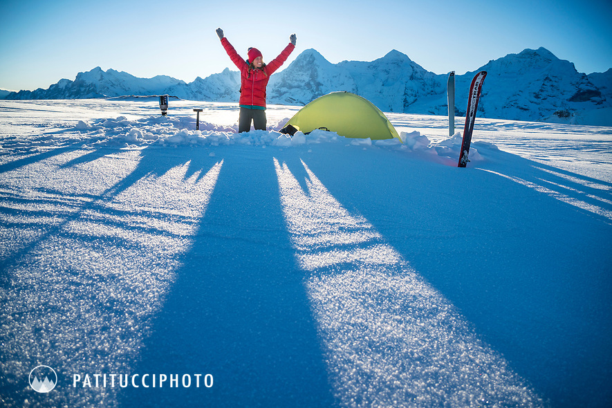A woman stands next to her tent and raises her arms with joy as the sun begins to warm her snow camp in the Jungfrau Region of Switzerland.