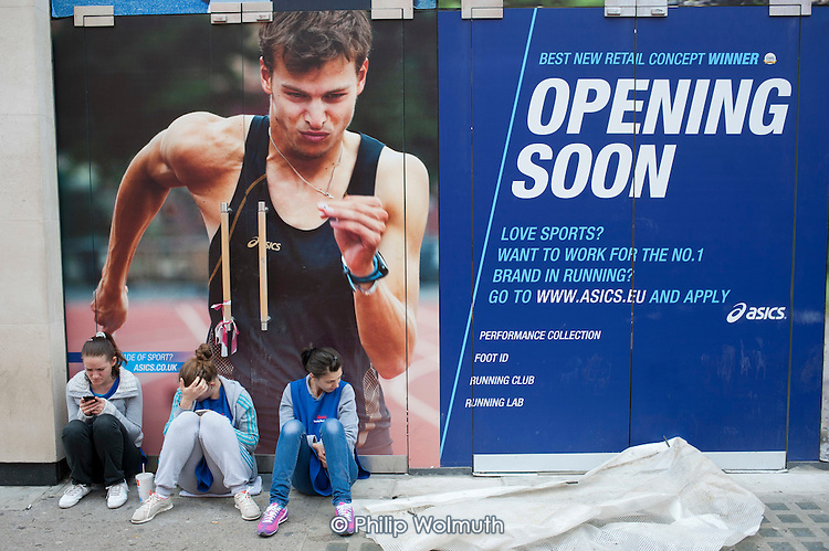 Advert for Japanese sports footwear company ASICS on a shopfront in Oxford Street, London.