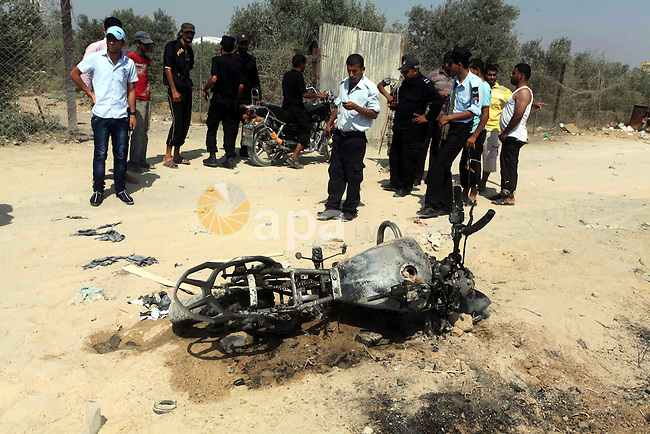 Hamas policemen stands near a  motorcycle that was hit in an Israeli air strike in Dir al-Balah in the central Gaza Strip June 19, 2012. An Israeli army statement said the Israeli air force targeted Palestinian militants in the central Gaza Strip on Tuesday, who were responsible for firing rockets into Israel earlier today. Photo by Ashraf Amra