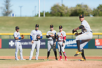Surprise Saguaros infielders Santiago Espinal (6), Charles Leblanc (12), Will Craig (45), and Andy Young (29) watch as relief pitcher Geoff Hartlieb (70) warms up during an Arizona Fall League game against the Mesa Solar Sox at Sloan Park on November 15, 2018 in Mesa, Arizona. Mesa defeated Surprise 11-10. (Zachary Lucy/Four Seam Images)