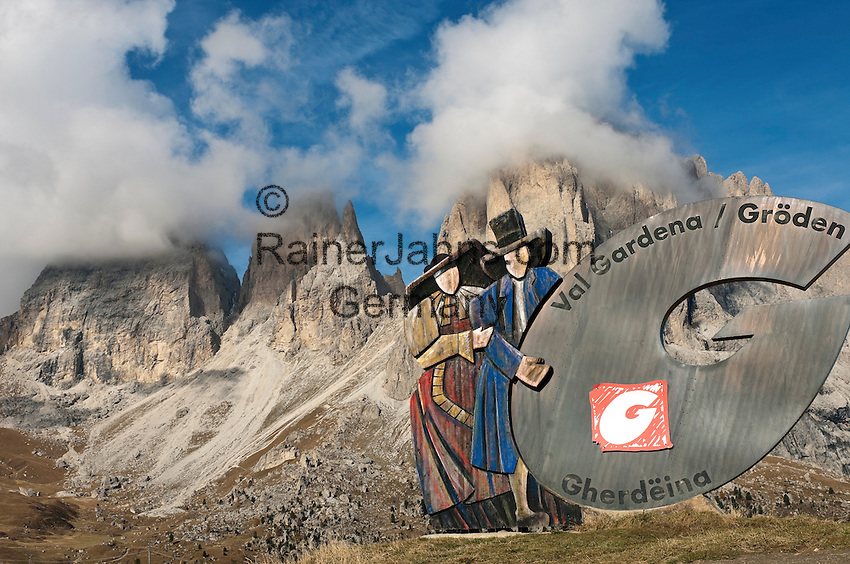 Italy, South Tyrol, Alto Adige, Dolomites, Val Gardena sign at Passo Sella mountain passroad with Sassolungo mountains | Italien, Suedtirol, Dolomiten, Hinweisschild am Sellajoch vorm Langkofel, hier beginnt das Groednertal